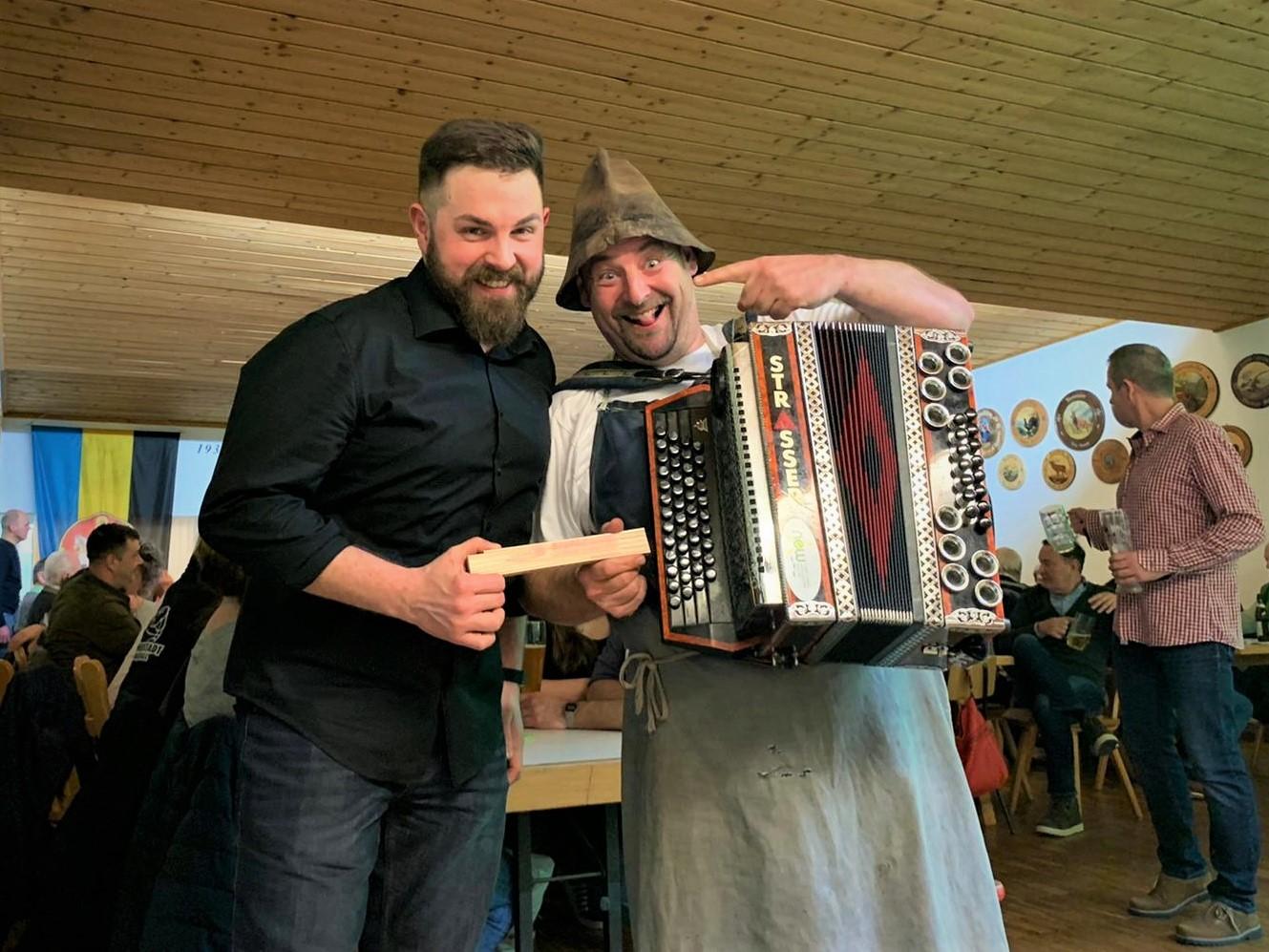 SPD-Bürgermeisterkandidat Sebastian Dippold übergibt Gstanzlsänger Lucky einen Meterstab der Neustädter SPD.